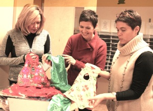 Patti Oldmixon, Kelli Pryor and Tania Strout unpack the Chinese School dance costumes, newly arrived from Shanghai, that will be used in the Feb 7th performances.